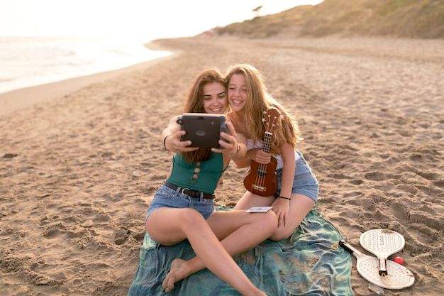 Female friends taking self portrait from instant camera at scenics beach