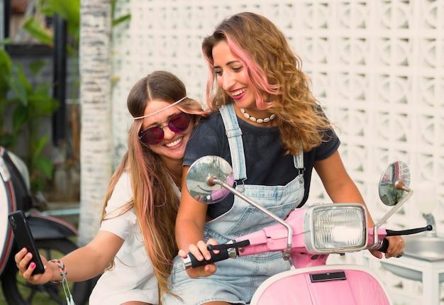 Amici femminili che prendono un selfie sullo scooter
