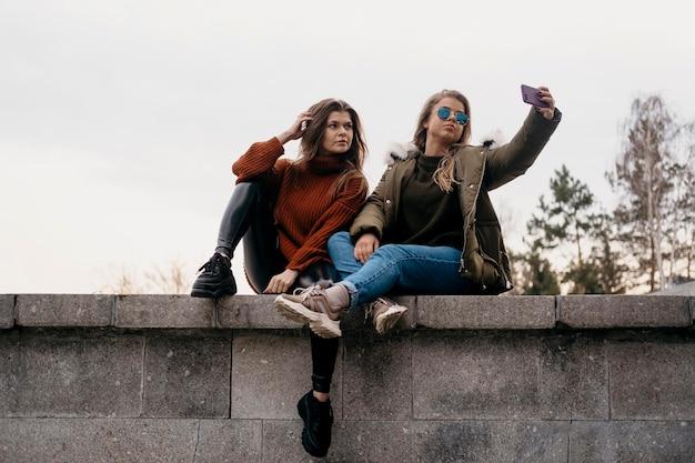 屋外で一緒に自分撮りをしている女性の友人