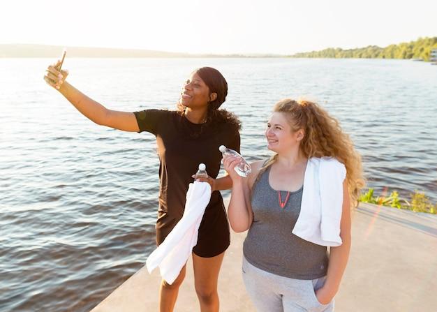 Подружки вместе делают селфи во время тренировки на берегу озера