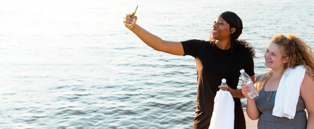 Amici femminili che prendono selfie mentre esercitano in riva al lago