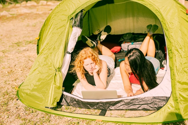 Female friends in tent using laptop