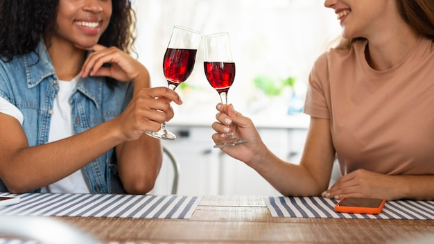 キッチンでグラスワインを乾杯する女性の友人
