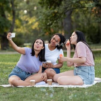 Подруги вместе в парке, делающие селфи