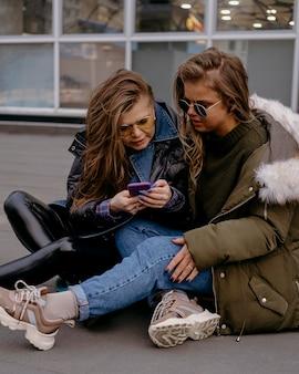 スマートフォンで屋外で一緒に女性の友人