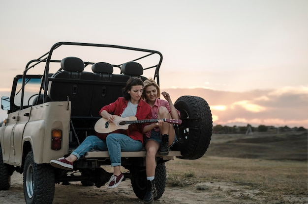Female friends traveling by car and playing guitar