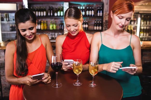 Female friends using mobile phone while enjoying wine