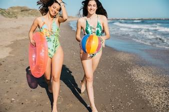 Женщины-друзья, идущие на пляже