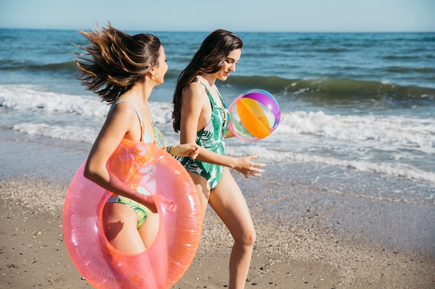 Female friends walking at the beach
