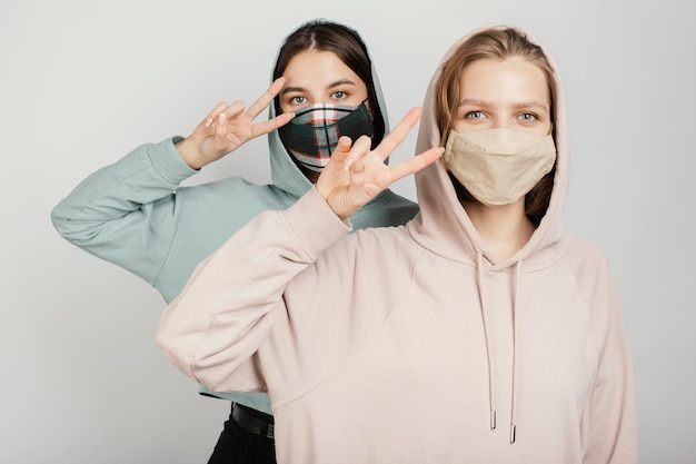 Female friends wearing masks and showing peace sign