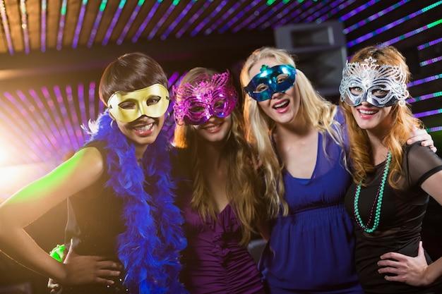 Female friends wearing masquerade in bar