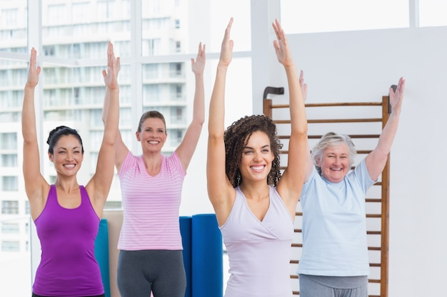 Female friends with arms raised exercising in gym