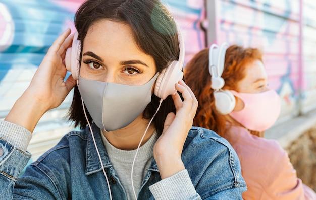 ヘッドフォンで音楽を聴いて屋外でフェイスマスクを持つ女性の友人