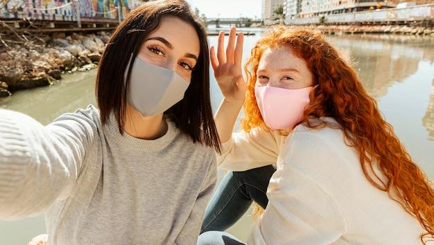 一緒に自分撮りをしている屋外のフェイスマスクを持つ女性の友人