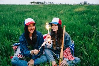 Женщины-друзья с фейерверком, сидящие в поле