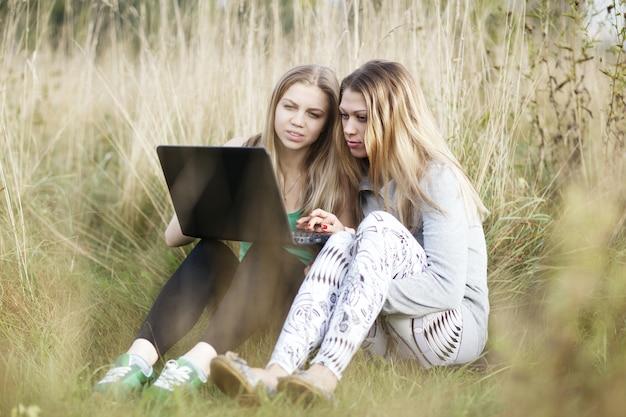 屋外のノートパソコンを持つ女性の友人