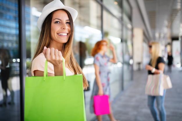 モールやお店で買い物を楽しみながら買い物袋を持った女性の友達