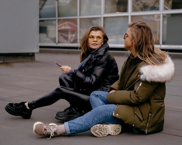 一緒に屋外でスマートフォンを持つ女性の友人