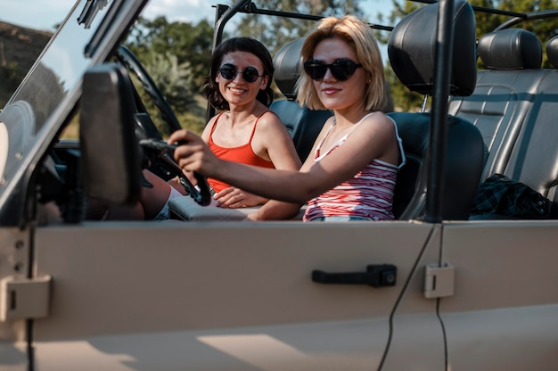 Amici femminili con occhiali da sole che viaggiano in auto