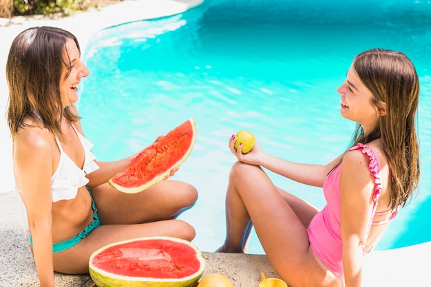 Female friends with tropical fruits near pool