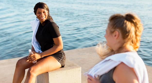 Amici femminili che lavorano insieme in riva al lago