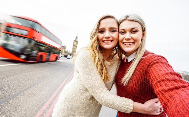Female friendship concept with girls couple taking selfie outdoors in london - dutch angle composition