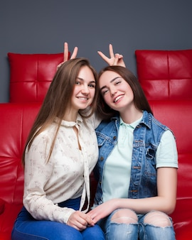 Женская дружба, досуг счастливых девушек. две красивые женщины, сидящие на красном кожаном диване