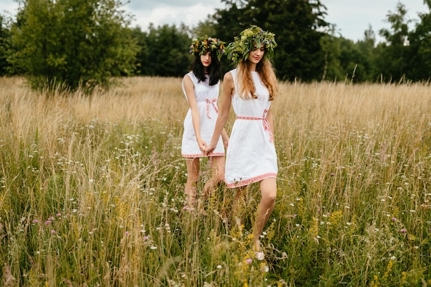 Female friendship. mood portrait of two beautiful slavonic appearance young girls in etnic  dresses and wreath of flowers walking at nature.