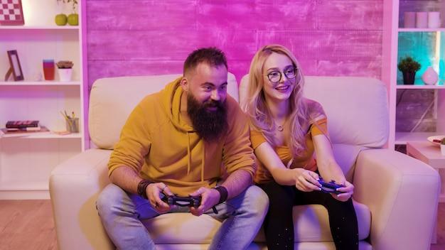 무선 컨트롤러를 사용하여 소파에 앉아 남자 친구와 온라인 비디오 게임을 하는 여성 게이머.