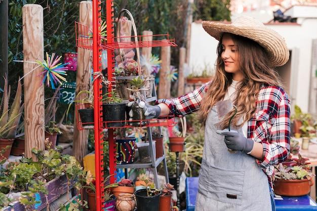 赤いラックに植物を配置する女性庭師