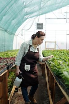 작업 중 큰 화단으로 구부리는 여성 정원사