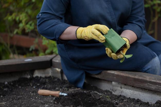 그녀의 정원에 심을 준비가 꽃 식물을 들고 여성 정원사