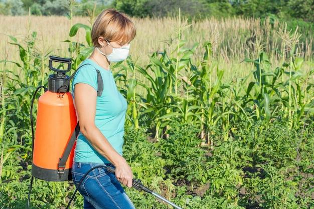 마스크를 쓴 여성 정원사는 정원에 있는 압력 분무기로 곰팡이 질병이나 해충으로부터 감자 식물을 보호하고 있습니다