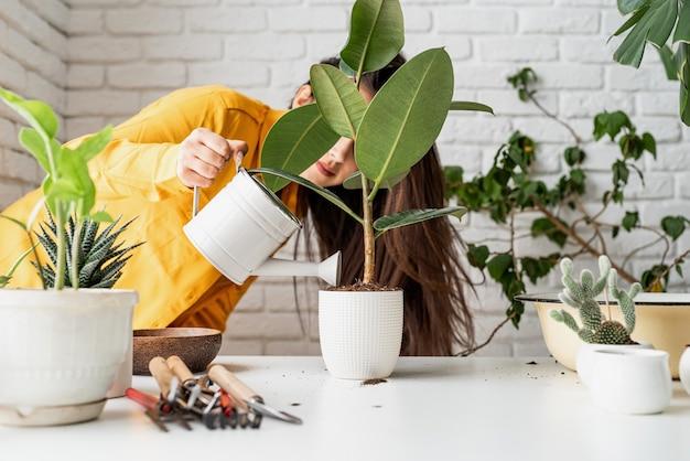 식물을 돌보는 노란색 옷을 입은 여성 정원사