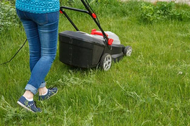 여성 정원사는 여름날 정원에서 잔디 깎는 기계로 작업하고 있습니다. 잔디 깎는 기계. 정원사 관리 작업 도구를 깎습니다.