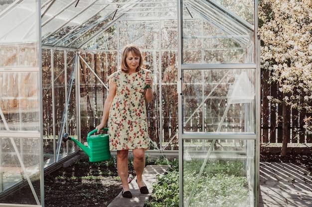 여성 정원사는 온실에서 식물에 물을 주고 있습니다. 그녀는 플라스틱 녹색 물뿌리개를 들고 있습니다.
