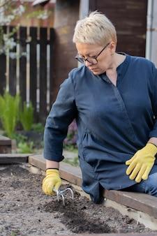여성 정원사는 그녀의 정원에서 식물을 심기 위해 화단에서 토양을 풉니 다.