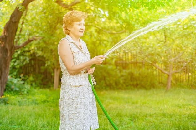 水ホースで庭に植物を注ぐ女性の庭師
