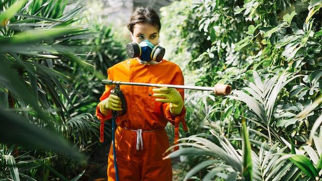 Женский садовник, распыляющий инсектицид на растении