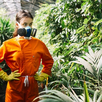 Female gardener wearing pollution mask looking at plants in greenhouse