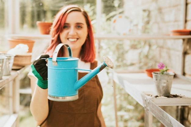 青いじょうろを持つ女性の庭師
