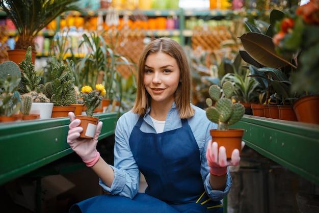 家の花を持つ女性の庭師、ガーデニングのための店。女性は花屋、売り手で植物を販売しています