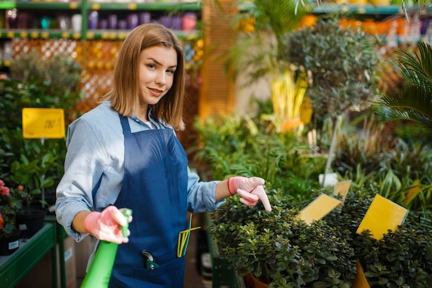 Female gardener with shovel takes care of plants in shop for gardening. woman in apron sells flowers in florist store