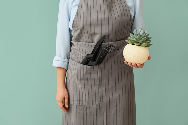 Female gardener with tools on color background