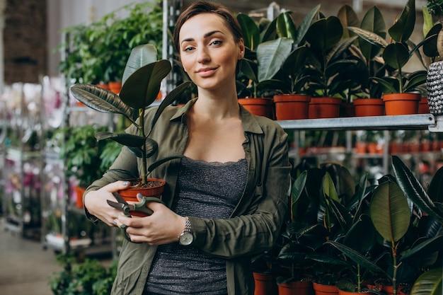 식물과 꽃을 가진 식물 집에서 여성 가드너