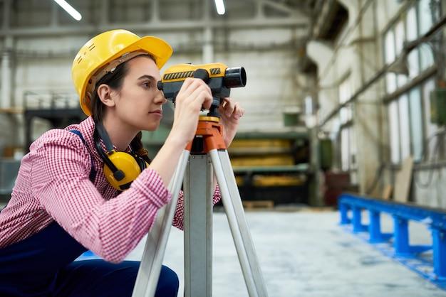 Female geodesist working on site
