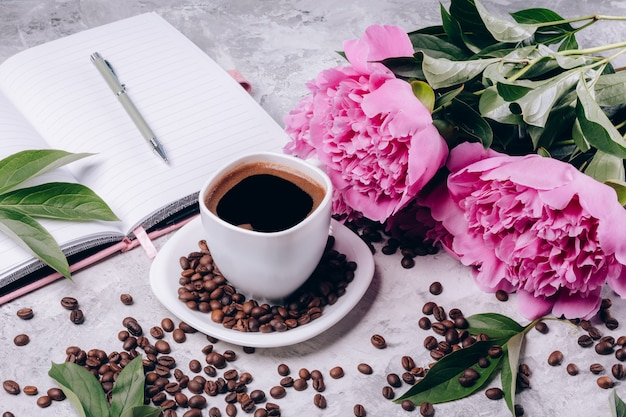 Female gift of coffee and peonies with notepad