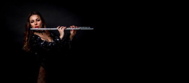 Художница девушки в костюме с флейтой на черной предпосылке. флейта в руке. игрок с оркестровым музыкальным инструментом. изолированные на черном. авторское пространство. большое фоновое пространство для надписи или логотипа