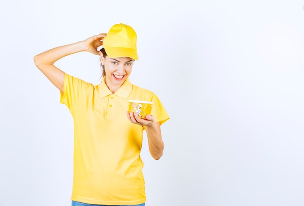 Девушка в желтой форме держит желтую чашку лапши на вынос.