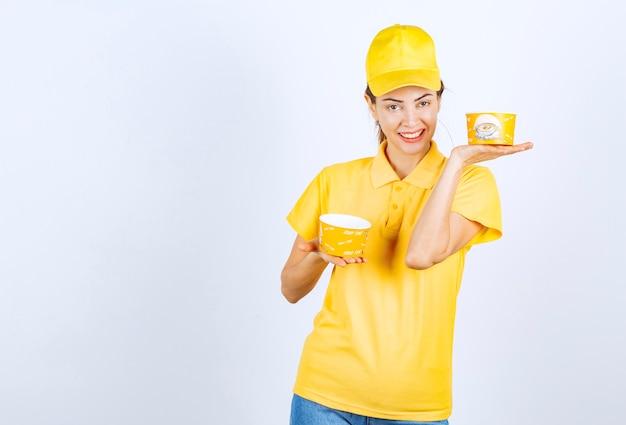 Девушка в желтой форме держит две чашки лапши на вынос.